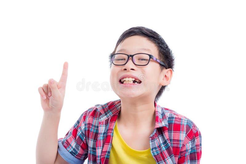 Ragazzo che indicano su e sorrisi sopra fondo bianco fotografia stock libera da diritti