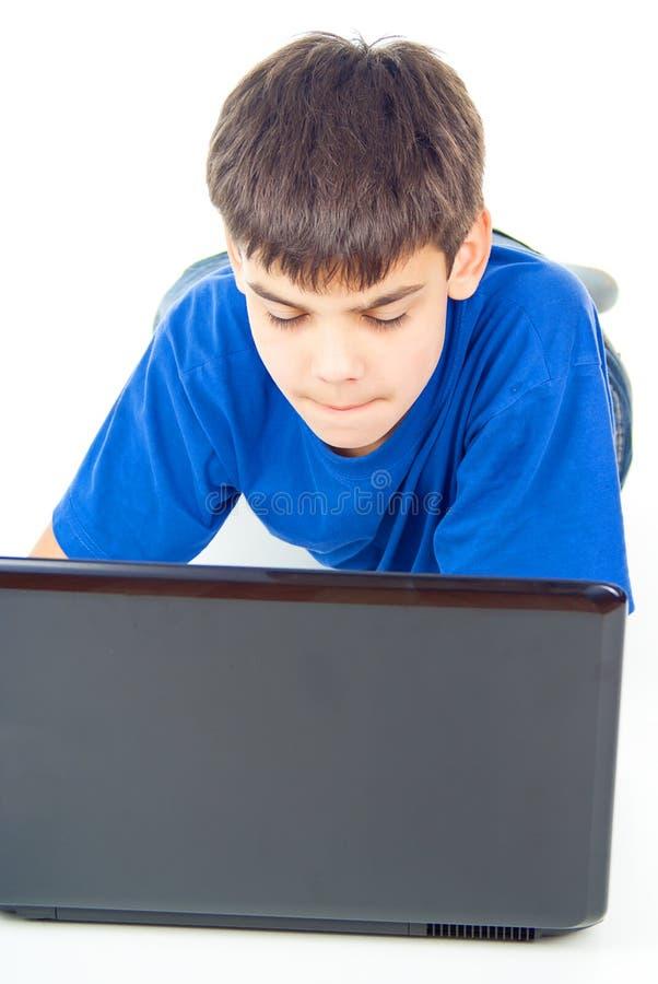 Ragazzo che lavora ad un computer portatile fotografia stock libera da diritti