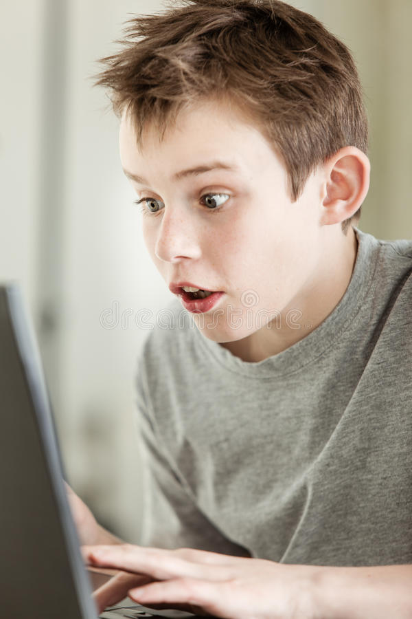 Ragazzo che lavora al computer portatile con il fronte stupito fotografia stock