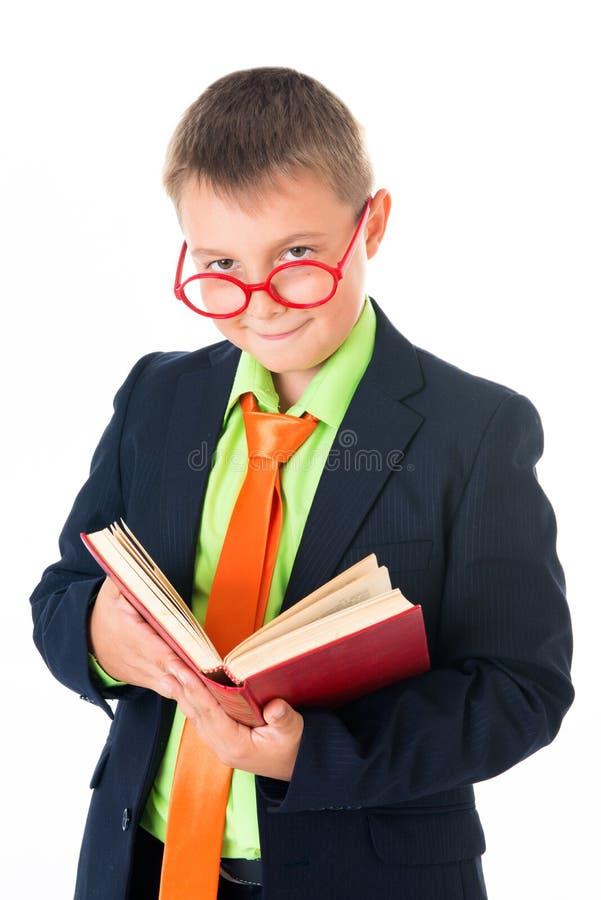 Ragazzo che legge un libro assetato per conoscenza - isolata sopra un fondo bianco fotografia stock libera da diritti