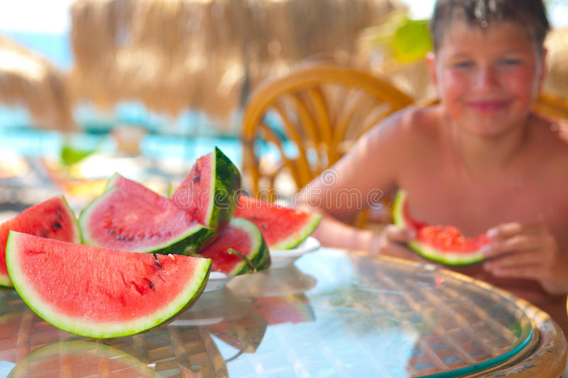 Ragazzo che mangia anguria affettata. fotografia stock