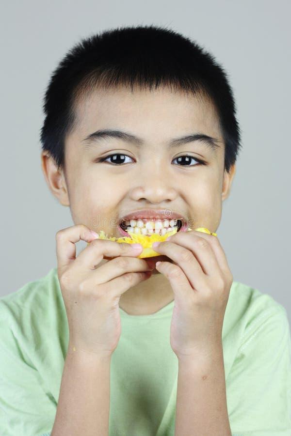 Ragazzo che mangia fetta arancione fotografie stock libere da diritti