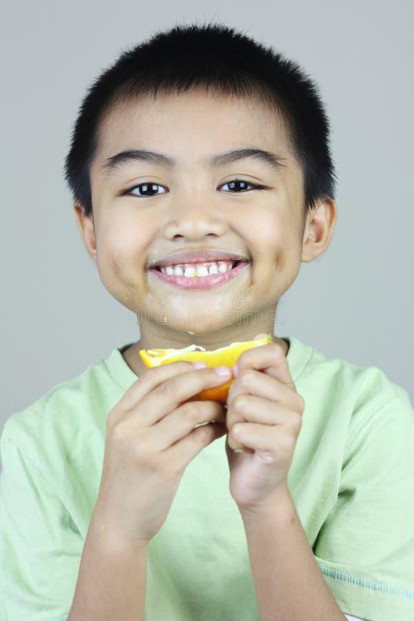 Ragazzo che mangia fetta arancione fotografia stock libera da diritti