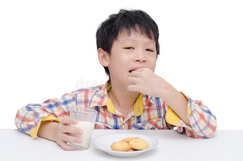 Ragazzo che mangia i biscotti con latte immagini stock libere da diritti