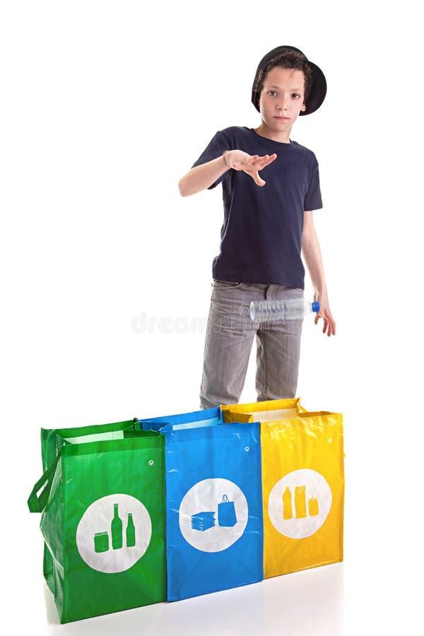 Ragazzo che mette una bottiglia di plastica per riciclare fotografie stock