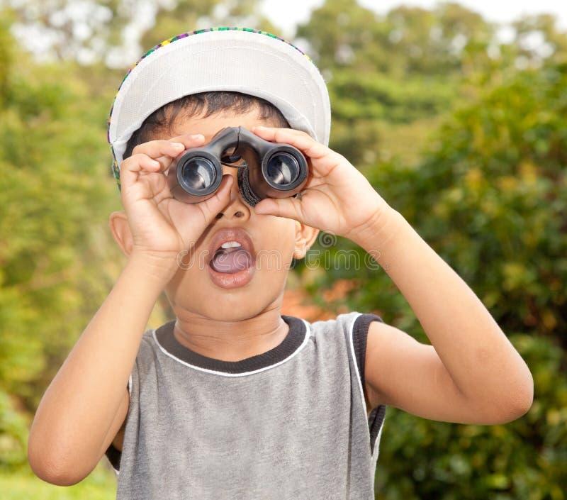 Ragazzo che osserva tramite il binocolo immagine stock