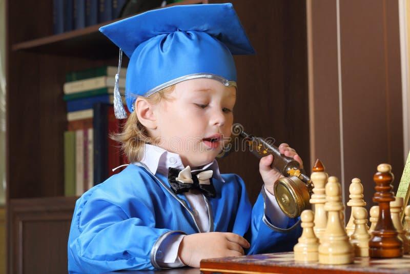 Ragazzo che parla sul telefono mentre giocando scacchi fotografia stock