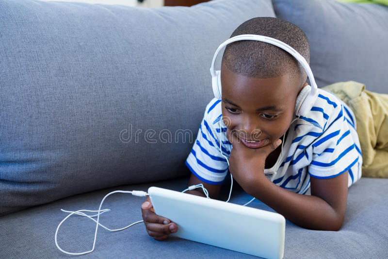 Ragazzo che per mezzo della compressa digitale mentre ascoltando le cuffie sul sofà a casa fotografia stock libera da diritti