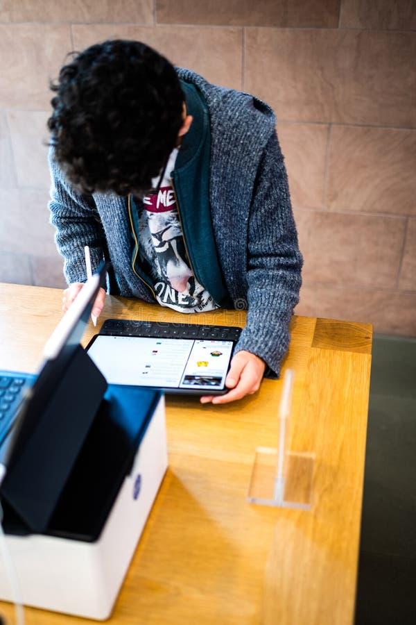 Ragazzo che per mezzo di pro compressa del nuovo iPad dei calcolatori Apple fotografia stock