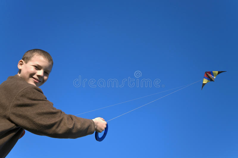 Ragazzo che pilota un'inclinazione di fine dell'aquilone fotografia stock