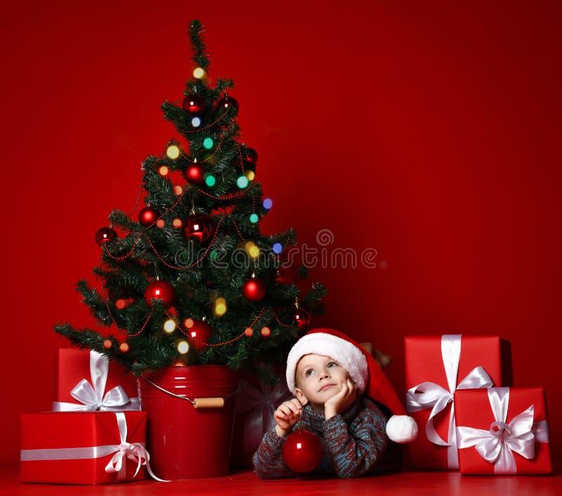 Ragazzo che posa in cappello rosso vicino all'albero di Natale fotografia stock libera da diritti