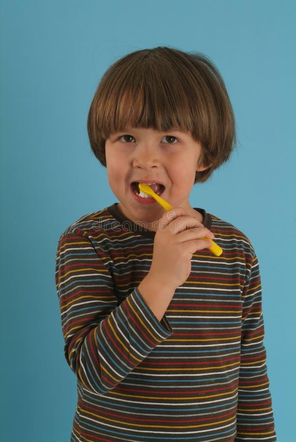 Ragazzo che pulisce i suoi denti immagine stock libera da diritti