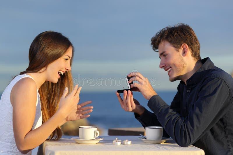 Ragazzo che richiede mano della sua amica con un anello di fidanzamento fotografia stock libera da diritti