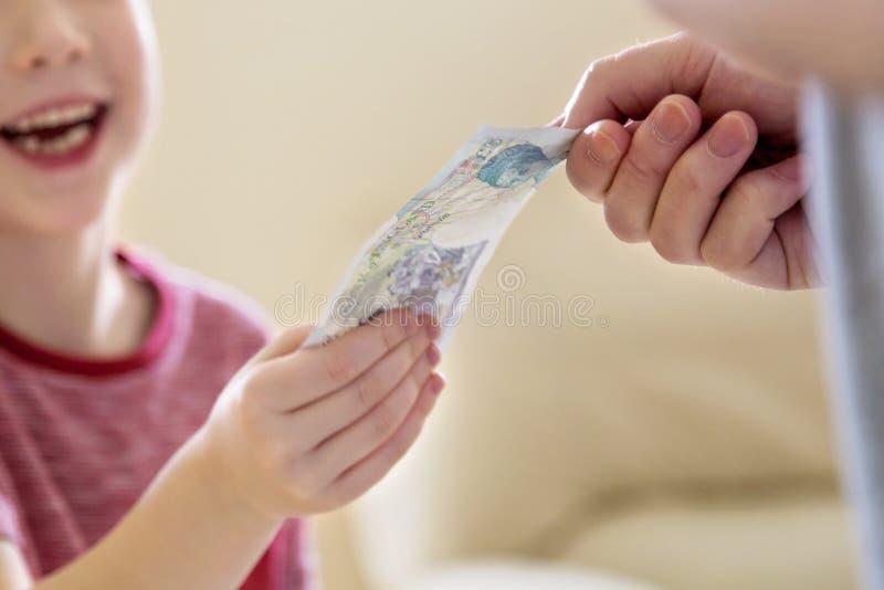 Ragazzo che riscuote denaro per piccole spese (indennità) dal padre fotografie stock