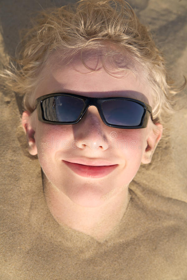 Ragazzo che si distende sulla spiaggia di estate in occhiali da sole fotografia stock