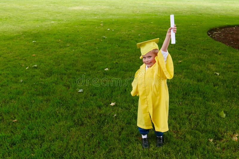 Ragazzo che si laurea dalla scuola materna fotografia stock libera da diritti