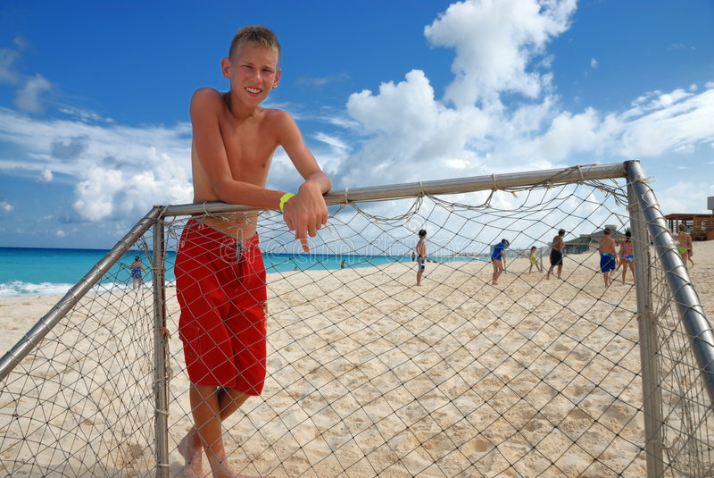 Ragazzo che si leva in piedi al palo della spiaggia fotografia stock
