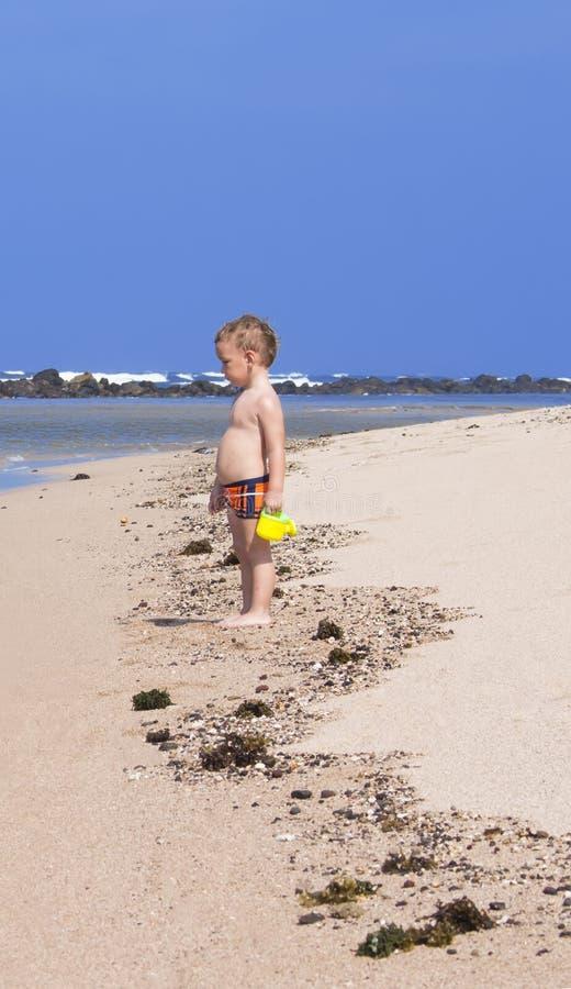 Ragazzo che si leva in piedi sulla spiaggia immagine stock libera da diritti
