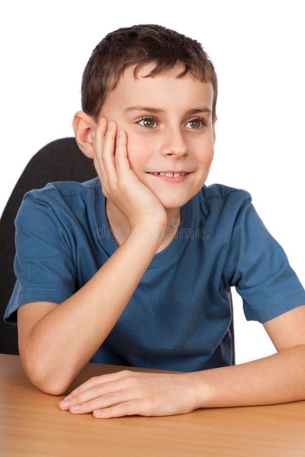 Ragazzo che si siede al suo scrittorio fotografia stock
