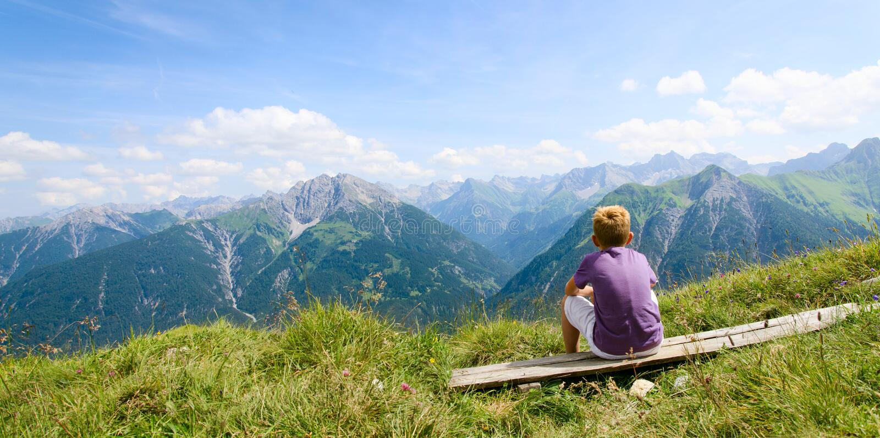 Ragazzo che si siede nelle montagne fotografie stock