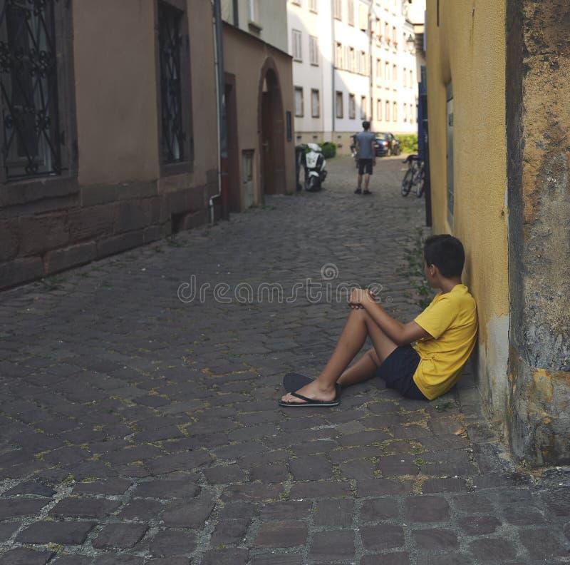 Ragazzo che si siede sul pavimento della via fotografia stock