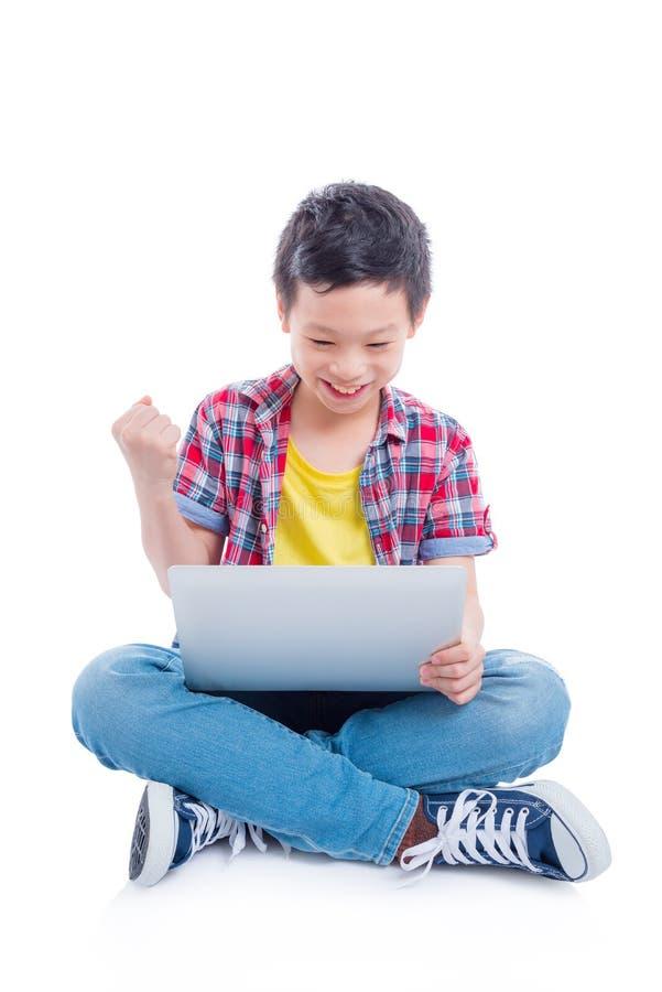 Ragazzo che si siede sul pavimento e che gioca sul computer portatile immagini stock