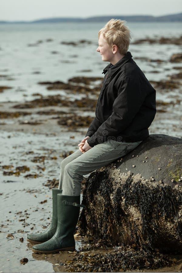 Ragazzo che si siede sulla vecchia roccia alla spiaggia fotografia stock libera da diritti