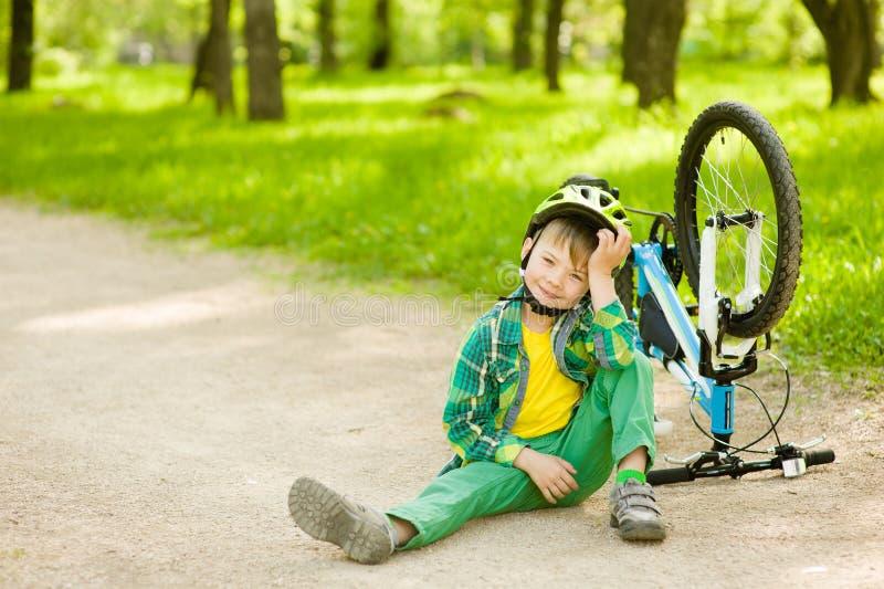 Ragazzo che si siede vicino ad una bicicletta rotta fotografia stock libera da diritti
