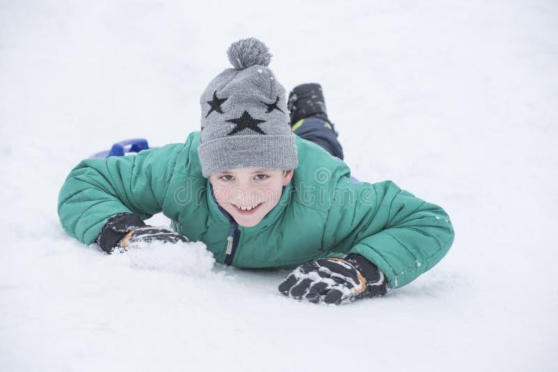 Ragazzo che si trova nella neve sulla suoi pancia e sorrisi primo piano del ritratto fotografia stock