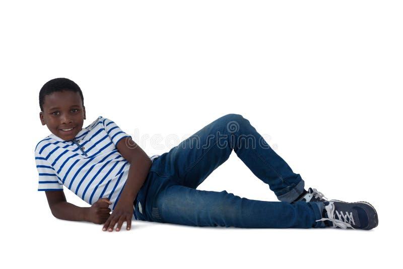Ragazzo che si trova sul pavimento contro il fondo bianco fotografia stock libera da diritti