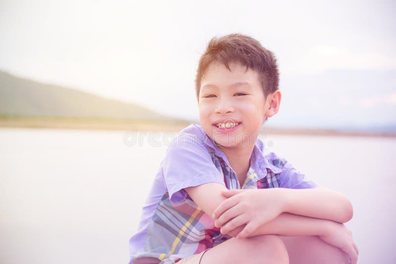 Ragazzo che sorride vicino dal fiume fotografia stock