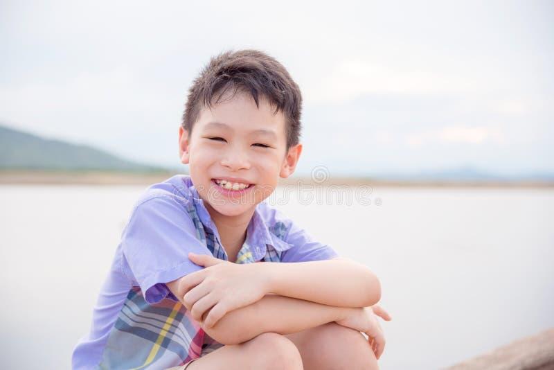 Ragazzo che sorride vicino dal fiume fotografie stock