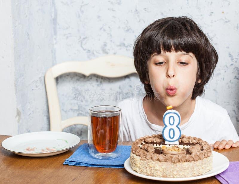 Ragazzo che spegne le candele sulla torta di compleanno fotografia stock libera da diritti