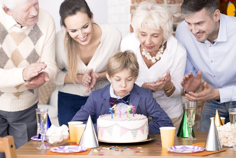 Ragazzo che spegne le candele sulla torta di compleanno immagine stock libera da diritti
