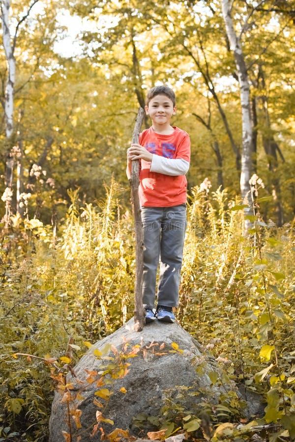 Ragazzo che sta su una roccia fotografie stock