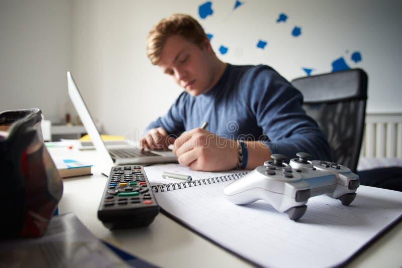 Ragazzo che studia nella camera da letto facendo uso del computer portatile immagini stock libere da diritti