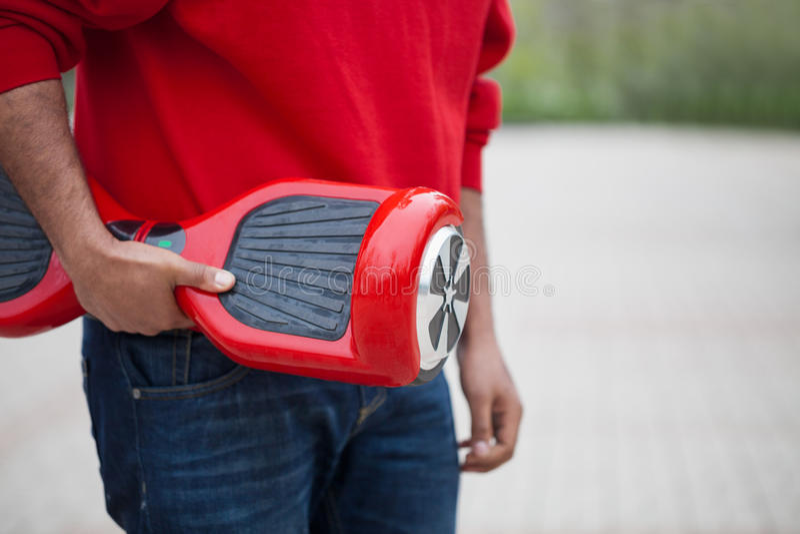 Ragazzo che tiene il mini motorino elettrico rosso moderno di librazione o segway del bordo fotografia stock libera da diritti