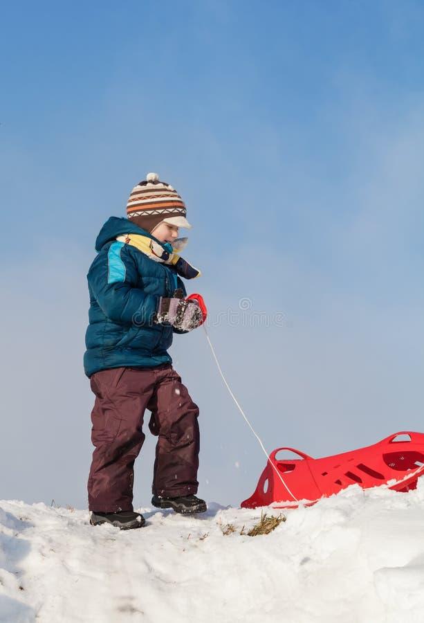 Ragazzo che tira slitta di plastica rossa verso una collina nevosa immagine stock