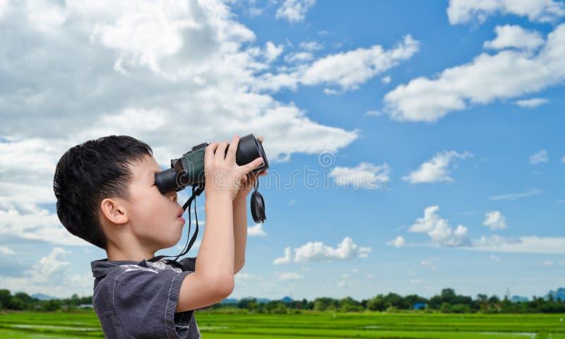 Ragazzo che utilizza il binocolo nel campo immagini stock libere da diritti