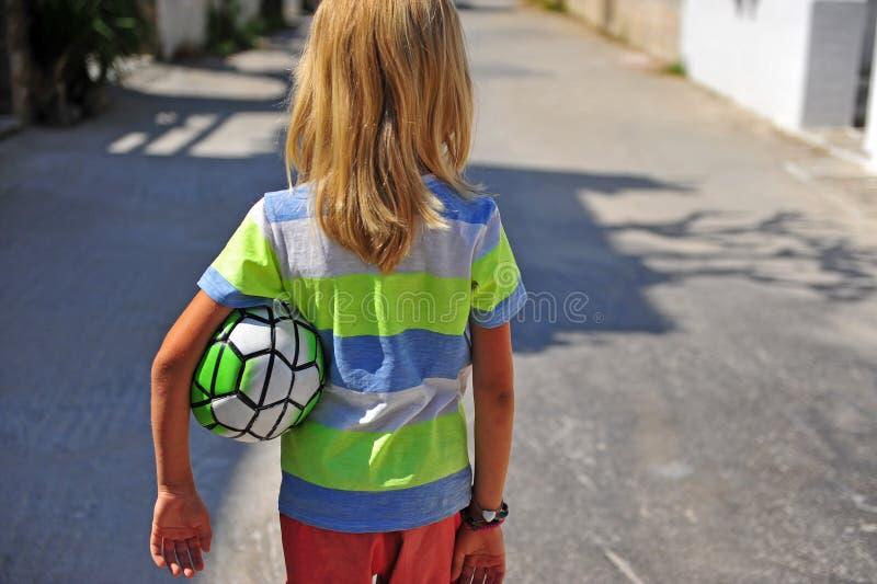 Ragazzo che va con il povero pallone da calcio immagini stock libere da diritti