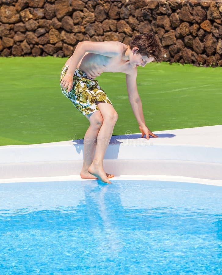 Ragazzo che verifica la temperatura dell'acqua dello stagno fotografia stock libera da diritti