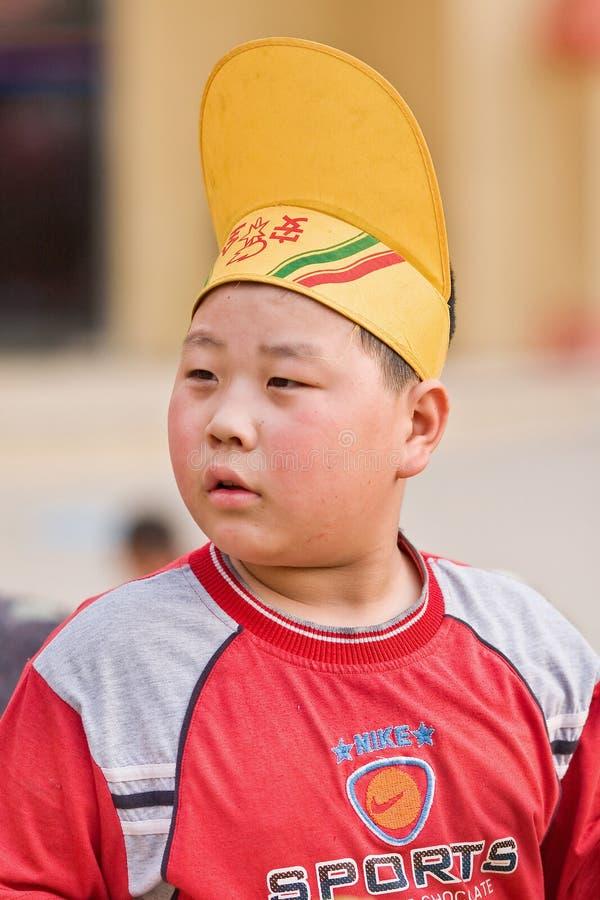 Ragazzo cinese di peso eccessivo con un cappello divertente, Pechino, Cina fotografia stock