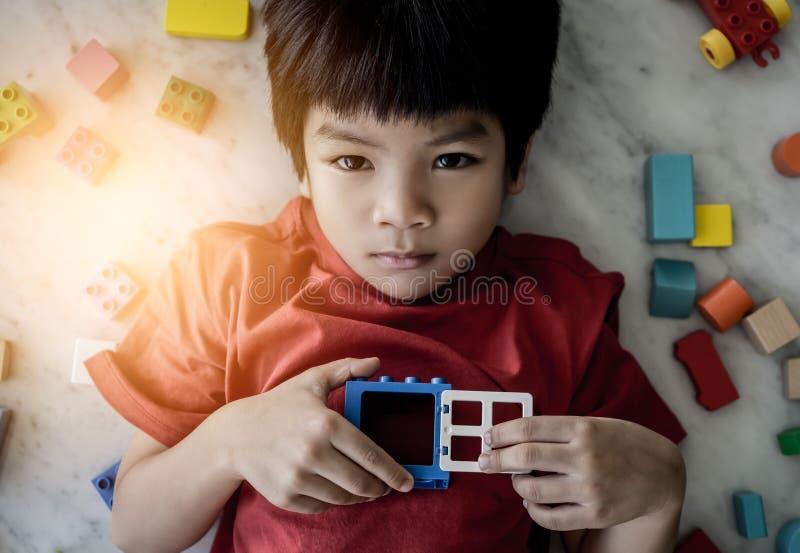 Ragazzo circondato dalle finestre aperte variopinte di vista superiore dei blocchetti del giocattolo al cuore fotografia stock