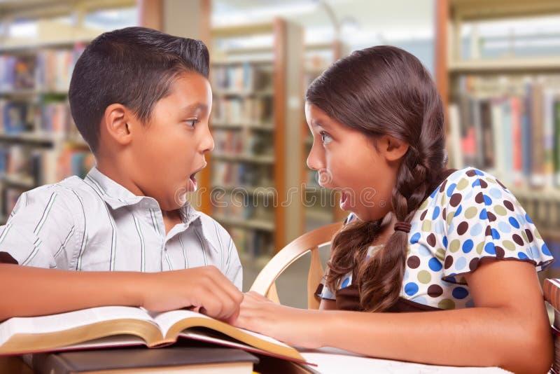 Ragazzo colpito e ragazza ispani che studiano insieme nella biblioteca immagine stock libera da diritti