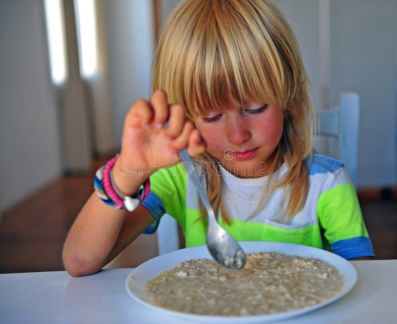 Ragazzo con capelli lunghi che mangiano porridge sulla prima colazione fotografia stock