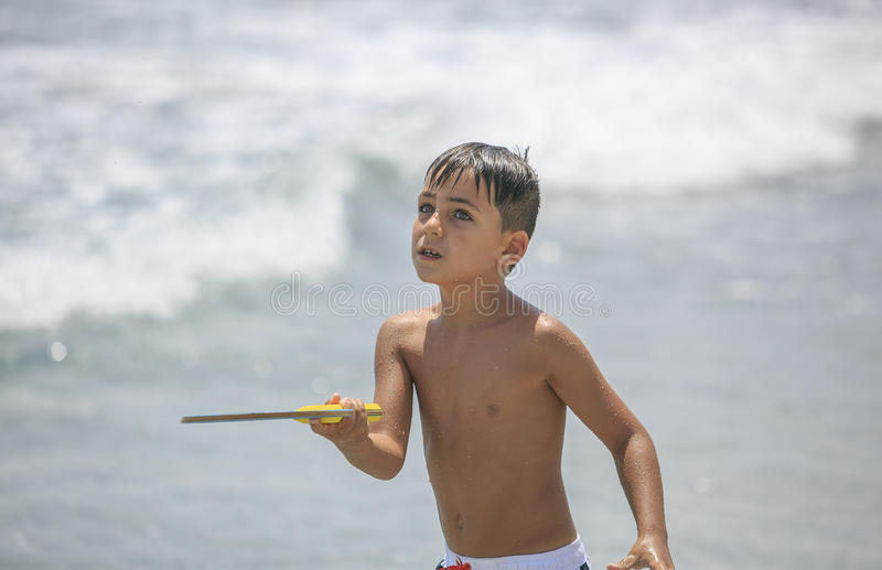 Ragazzo con gli occhi verdi che giocano a tennis sulla spiaggia immagini stock libere da diritti