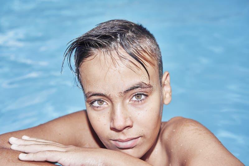 Ragazzo con gli occhi verdi nella piscina fotografia stock
