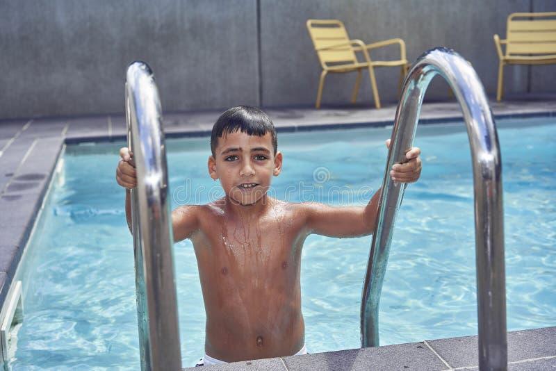 Ragazzo con gli occhi verdi nella piscina immagini stock