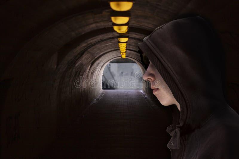 Ragazzo con il cappuccio che sta in un passaggio sotterraneo scuro con le lampadine della luce gialla al tetto ed alla luce all'e immagini stock