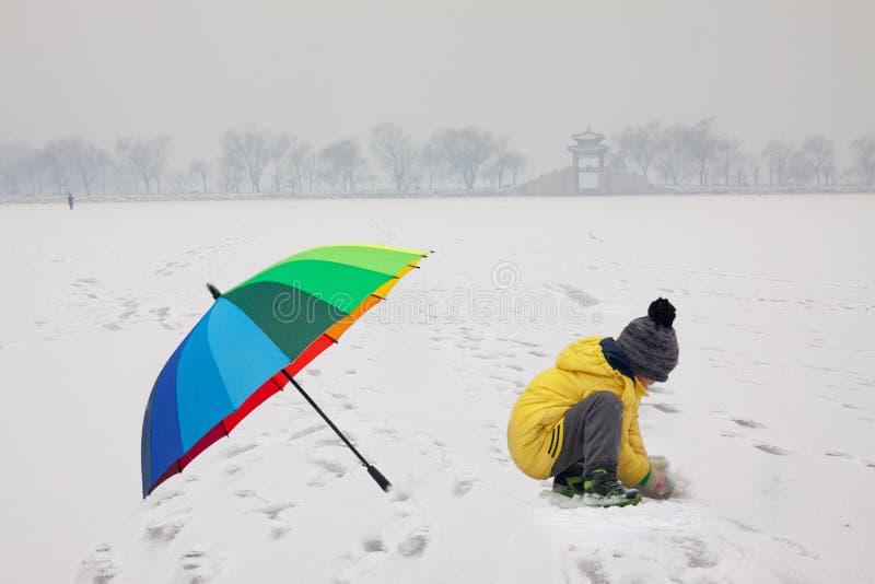 Ragazzo con l'ombrello nel palazzo di estate nevoso fotografia stock libera da diritti